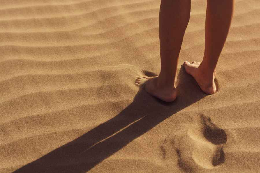 person stand on sand