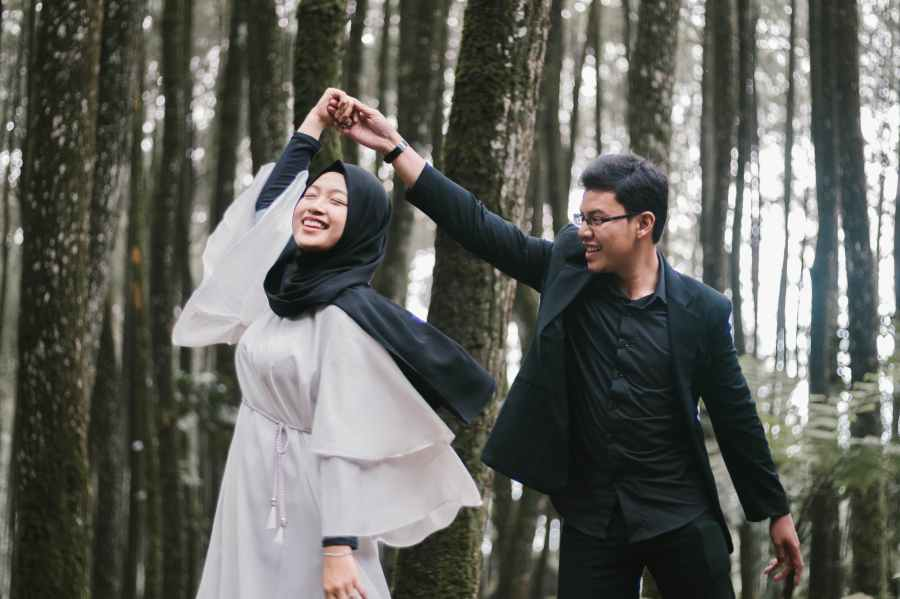 man and woman dancing near forest trees while smiling