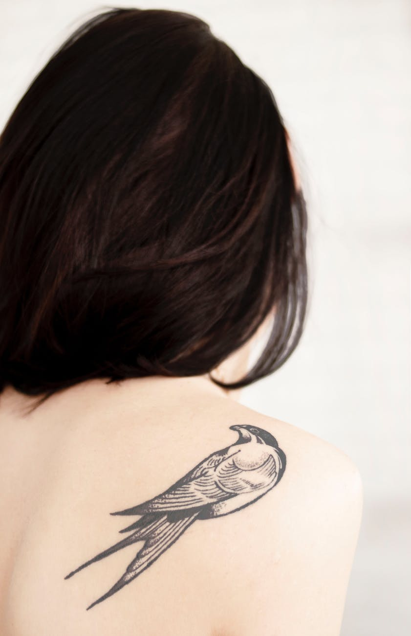 view of woman s back with bird tattoo on right shoulder