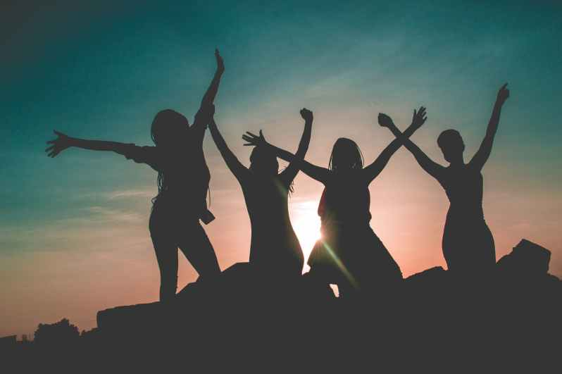 silhouette of four people against sun background